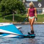Girl prepares to water ski as she stands on the Varatti boat surf gate.