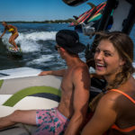 Group having fun and laughing with surfer behind Varatti boat.