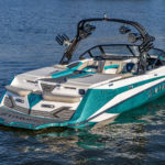 A teal and white FLOE Varatti wake boat sparkles off the crisp lake water